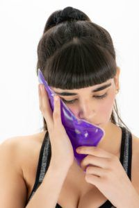 Woman using an ice pack on her jaw