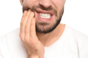 Man with tooth pain holding his lower jaw