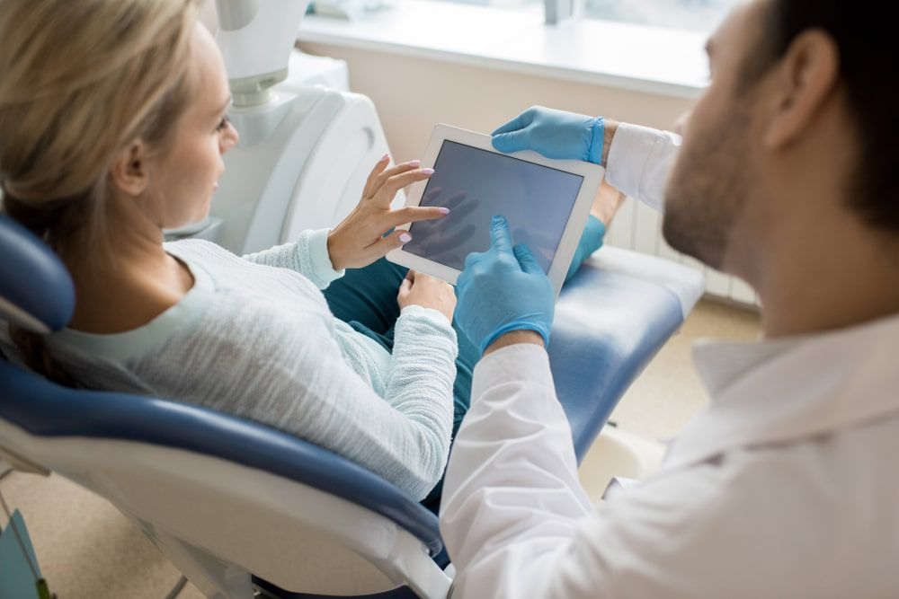 Dentist talking to patient and referencing something on a tablet