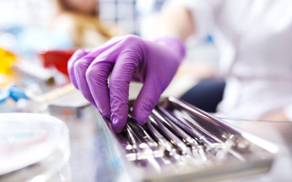 Purple glove reaching for dental tools